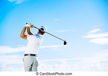 Man Playing Golf - Man Swinging Golf Club with Blue Sky...