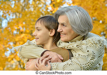 Grandmother with boy in the autumn park