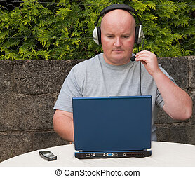 middle age man using laptop and voip , advert on laptop