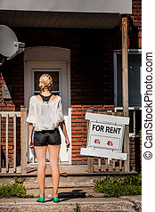 Young Woman standing in front of her new apartment - Young...