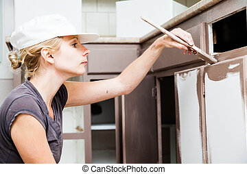 Closeup of Woman Painting Kitchen Cabinets - Closeup of...
