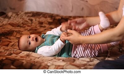 Helping Baby to Sit Up - Mother helps little baby to sit up.