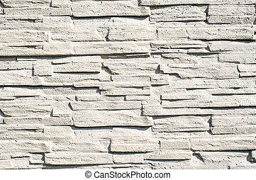 A fence made of narrow stones fastened by cement painted with wh