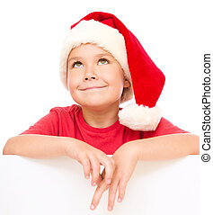 Little girl in santa hat is holding blank board and smiling,...