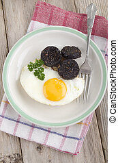 black pudding and fried egg on british breakfast muffin