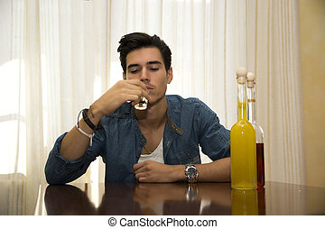 Young man sitting drinking alone at a table with two bottles...
