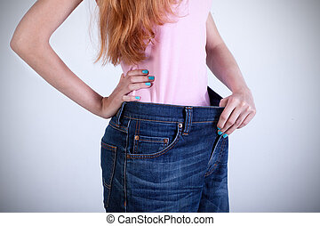 Woman trying on her old big jeans - Dieting woman trying on...