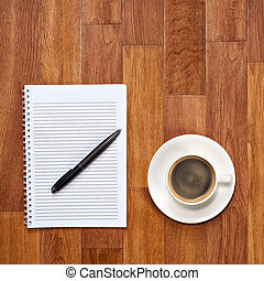 Blank notepad with office supplies and cup of coffee on wooden t