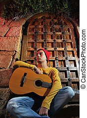musician with his guitar sitting on a medieval gate