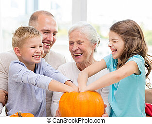 happy family sitting with pumpkins at home - family,...