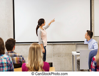 group of students and smiling teacher in classroom -...