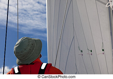 Sailing - A sailor looking at sails, checking the trimming.
