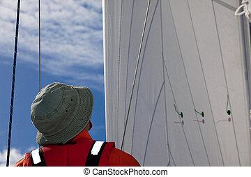 Sailing - A sailor looking at sails, checking the trimming.