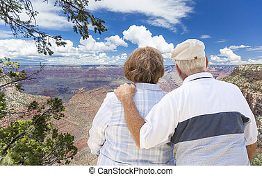 Happy Senior Couple Looking Out Over The Grand Canyon -...