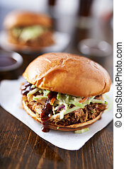 barbecue pulled pork sandwiches with cole slaw on wood table