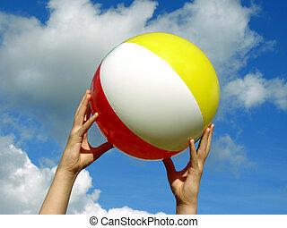 hands with beach ball against blue sky...