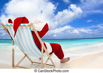 Santa Claus sitting on beach chairs with blue sky and...