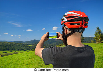 Cyclist taking pictures with smart phone - Cyclist taking...