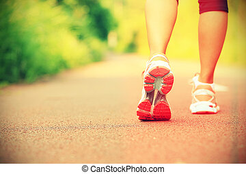 young fit woman running at forest
