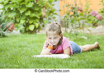 Girl reading a book in the park laid down on the grass