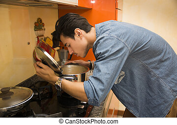Young man smelling the food in the pot as he cooks his...