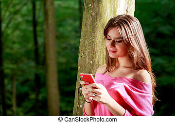 Young beautiful woman with toothy smile send a text message...