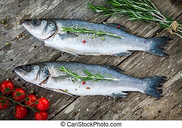 Two raw seabass with cherry tomatoes and rosemary - Two raw...