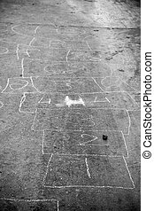 Hopscotch game drawn out on a road surface with white crayon...