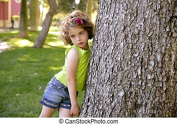 Beautiful little brunette girl beside a tree trunk -...