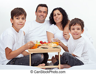 Family with two boys having breakfast in bed