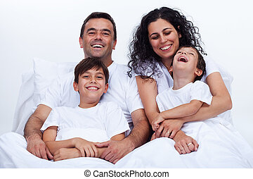 Happy family with two boys cuddling in bed on a lazy morning