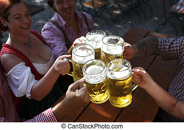 People drinking beer in a traditional Bavarian beer garden -...