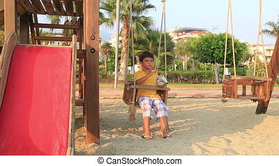 child eating chips - Boy eating chips on swing