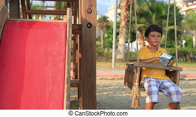 child eating chips - Sad lonely boy eating chips on swing