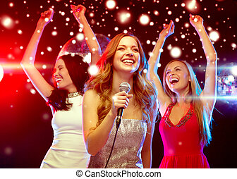 three smiling women dancing and singing karaoke - party, new...