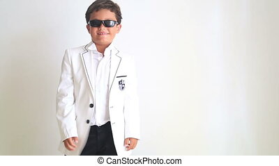 Fashionable boy with sun glasses turn around and pointing