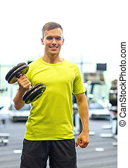smiling man with dumbbell in gym - sport, fitness, lifestyle...