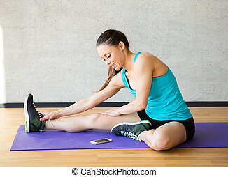smiling woman stretching leg on mat in gym - fitness, sport,...