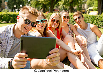 smiling friends with tablet pc making selfie - friendship,...