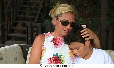 Cute boy sleeping on mother's arms