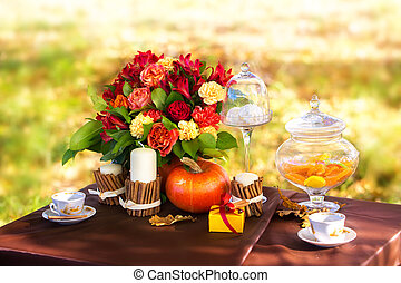 Decorated table for a romantic dinner in autumn Park