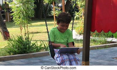 child using digital tablet - child swinging and using...