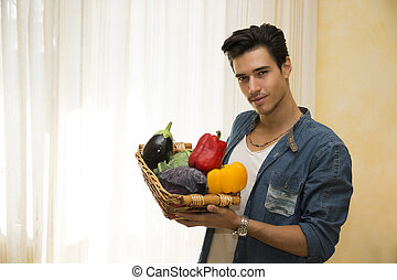 Young man holding a basket of fresh vegetables, healthy diet...