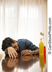 Young man drunk and sleeping alone at a table with two...