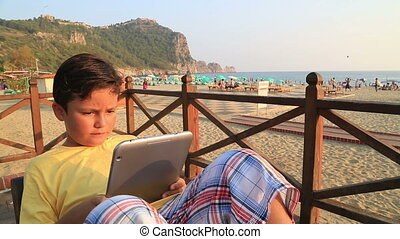 child with digital tablet on the beach