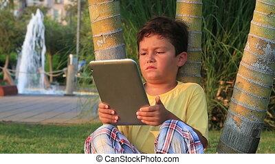 Cute kid using digital tablet at the park