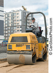 Road roller during road works - Construction worker...