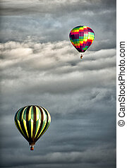 two hot air balloons in clouds