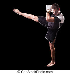 High Kick - a young kickboxer or boxer isolated over a black...