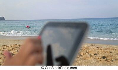 woman hands holding digital tablet on the beach